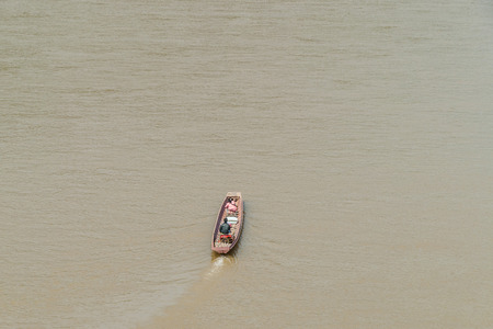Couple crossing the muddy Mekong river by long boat