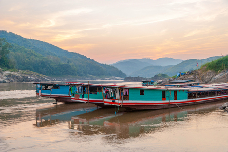 Long boats for a ride down the river Mekong at river bank in late afternoon sun, Mekong river, Laos