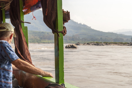 Man looking over the Mekong river and its scenery from the long boat traveling towards Luang Prabang Stock Photo
