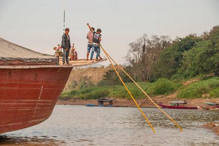 Nakaraj Nakhon, Laos - Feb 2016: Laotians pushing the ship with big poles over the Mekong river