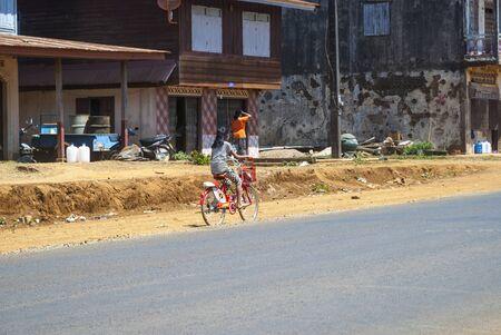 Pakse, Laos - Feb 2016: Girl riding a bike along the road in village in Laos Reklamní fotografie