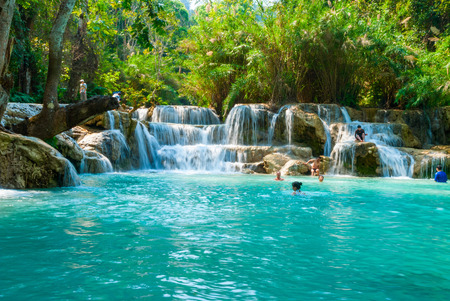 Luang Prabang, Laos - Feb 2016: People swimming in the water and visiting Kuang Si waterfalls, one of the biggest attractions in the area