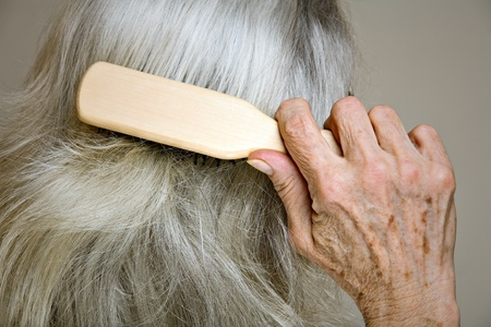 Senior woman brushing her hair - closeup detail photo
