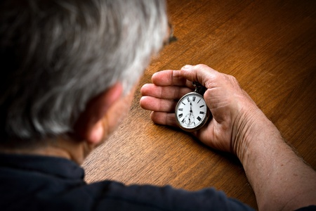 Pocket watch in senior mans hand