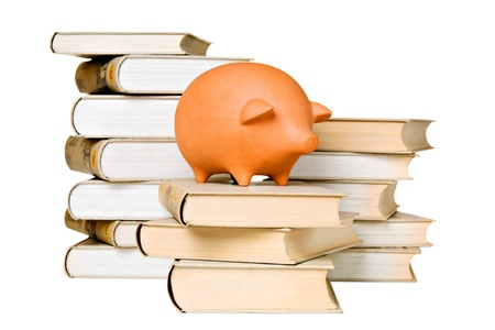 Clay piggy bank and old-fashioned books, isolated on white photo