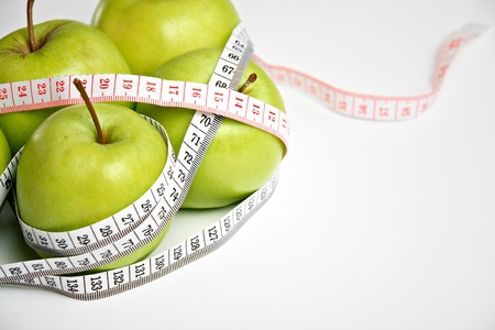 Fresh green apples with measuring tape photo