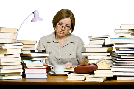 Middle aged woman sitting behind the desk, reading books  photo