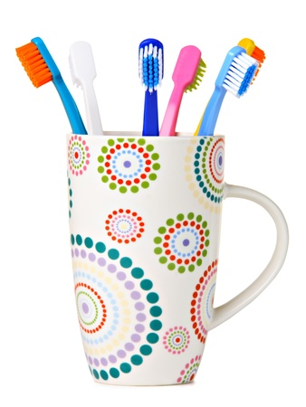 Tooth Brushes in ceramic cup, isolated on white