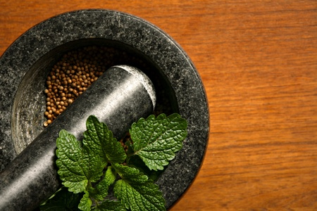 Mortar with coriander and mint on wooden table photo