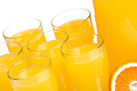 Pitcher and glasses full of juice, isolated on white photo