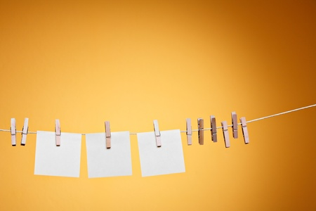 clothes pegs: Three blank notes hanging against orange wall  Stock Photo