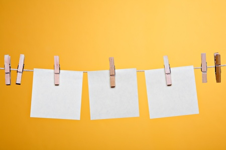 Three blank notes hanging against orange wall  Stock Photo