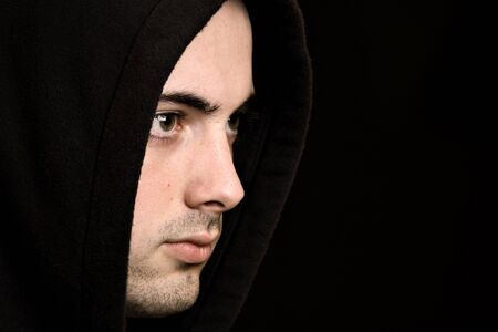 good looks: Handsome young man with hood, against black background