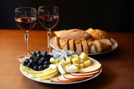 Cheese and wine on wooden table photo