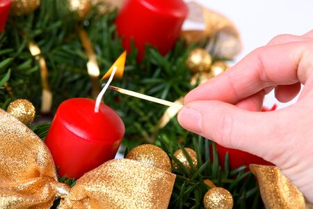 Human hand lightning the candles on advent wreath Stock Photo