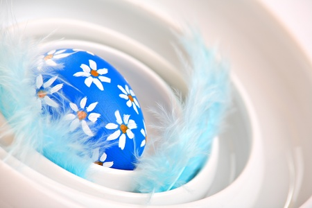 Beautiful hand painted easter egg with feathers, in ceramic bowl photo