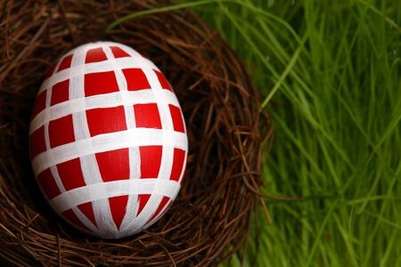 Red hand-painted Easter egg in nest on the grass  photo