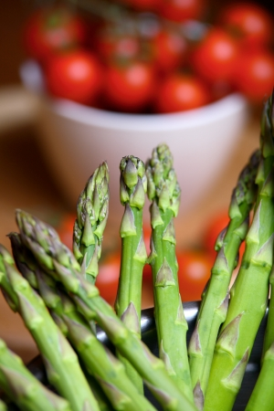 Asparagus with cherry tomatoes in the background photo