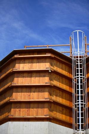 Wooden silos against blue cloudy sky photo