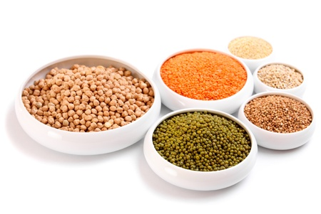 Millet, barley, buckwheat grains, red lentil, green soybeans and chick peas in ceramic bowls, isolated on white  photo