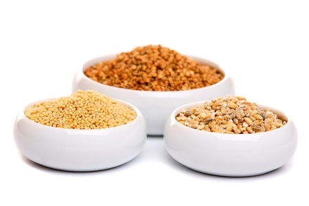 Millet, buckwheat grains and barley in ceramic bowls, isolated on white  photo
