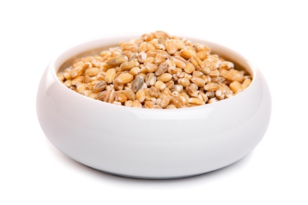 Barley in ceramic bowl, isolated on white  photo