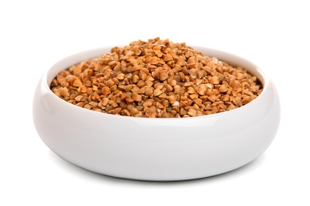 buckwheat: Buckwheat grains in ceramic bowl, isolated on white  Stock Photo