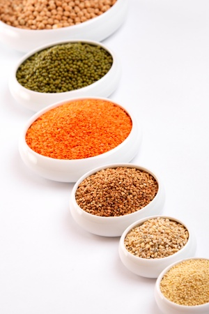 Millet, barley, buckwheat grains, red lentil, green soybeans and chick peas in ceramic bowls photo