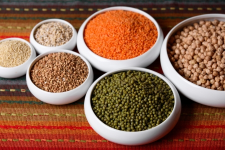 pulses: Millet, barley, buckwheat grains, red lentil, green soybeans and chick peas in ceramic bowls