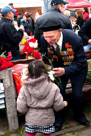 RIGA,LATVIA - MAY 9: Russian Veteran of World war II receiving flowers from a girl on the parade May 9, 2010 in Riga,Latvia.