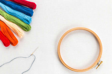 Embroidery hoop, needle and different color of thread for sewing lying on a white background. Set for needlework top view
