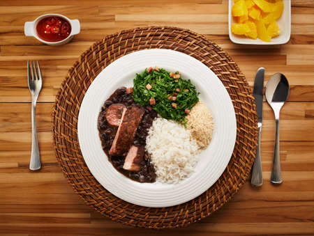 meat dish: Brazilian feijoada dish on rustic table