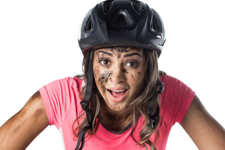 Woman covered in mud when riding a bike Imagens
