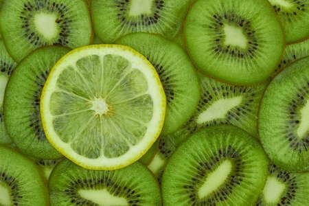 One lemon slice on kiwi background