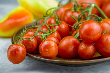 Close up view of red cherry tomatoes bunch in a plate and yellow sweet pepper on the background