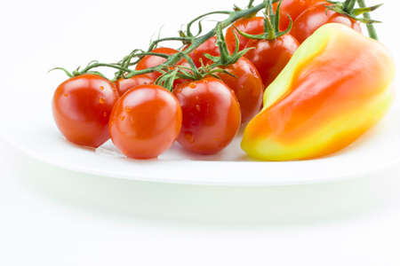 Bunch of fresh red tomatoes and yellow sweet pepper on a plate Close up view, white background. Healthy food concept.