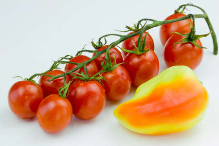 Bunch of red cherry tomatoes with water drops and yellow sweet pepper isolated on a white background. Close up view