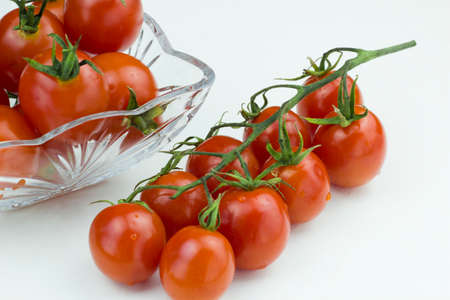 Bunch of red cherry tomatoes and tomatoes in glass bowl isolated on a white background Stock Photo