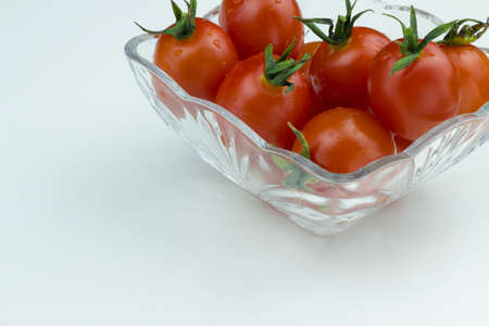 Fresh red cherry tomatoes with water drops in a glass bowl on a white background. Close up view, isolated tomatoes