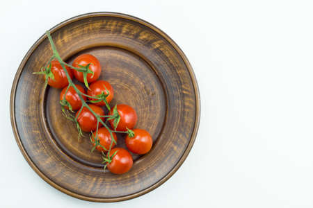 Top view of red cherry tomatoes bunch with water drops on brown plate isolated on a white background. Close up view Stock Photo
