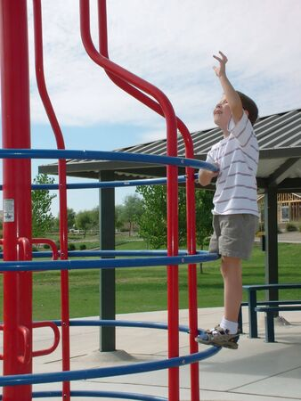 jungle gym: Little boy climbing to the top of a Jungle Gym Stock Photo