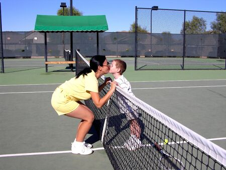 lady and boy kissing at tennis net Stok Fotoğraf