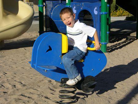 gleeful: Boy riding toy at playground