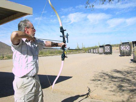 senior olympics: Senior competitive archer at archery range Stock Photo