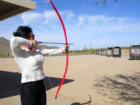 bowman: Lady at archery range shooting targets Stock Photo