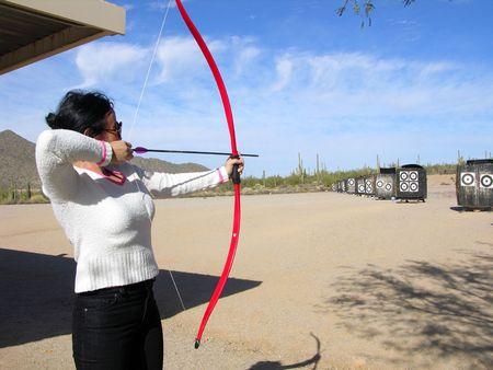 Lady at archery range shooting targets Stock Photo