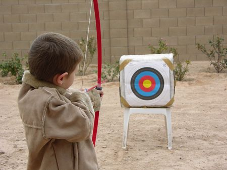Boy shooting arrow at target