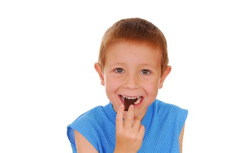 bisquit: Young boy eating a piece of chocolate Stock Photo