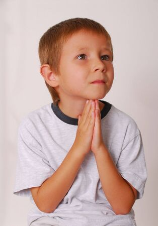 bowed head: Boy praying and looking upwards Stock Photo