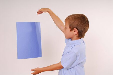 Boy magically holding sign floating in air Stok Fotoğraf